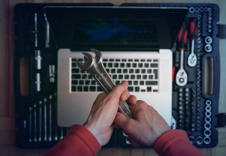 Hands holding two wrenches above a laptop, representing software tools